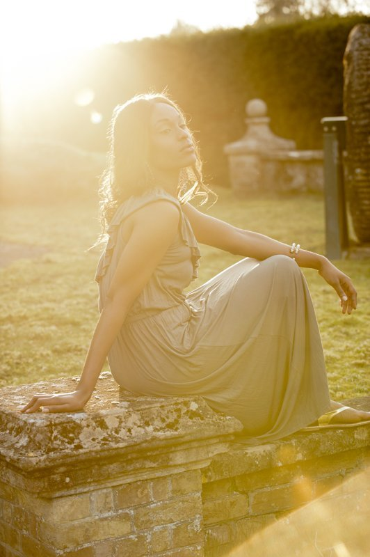Fashion picture of young woman outdoors with sunlight flare