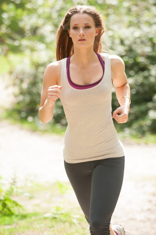 Woman running outdoors in fitness outfit