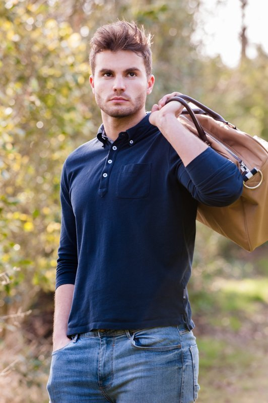 Man in countryside scene holding bag